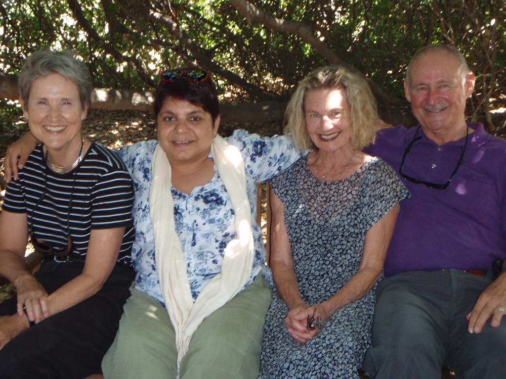 Margaret Magnus, Mehera Arjani, Maureen Lehman, and Sam Ervin under Baba's Tree during Mehera's 2014 visit. (Marta Flores photo, 2014.)