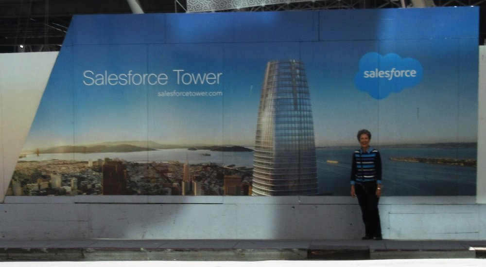 VOLUNTEER DATABASE ADMINISTRATOR Margaret Magnus in front of a photo of the new Salesforce Tower under construction in San Francisco, September 2016. (Photo: Sam Ervin)