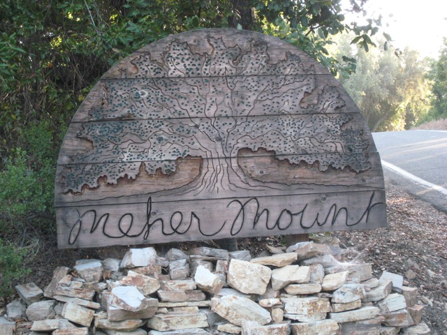 HAND-CARVED, WOOD SIGN created by former Board member Jim Auster at the entryway to Meher Mount for many, many years. (Photo: Sam Ervin, 2015)