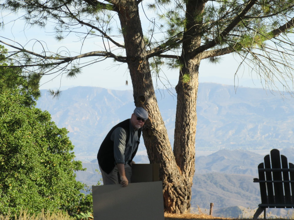 BYRON PINCKERT, consulting architect for Meher Mount, holding cardboard cutouts the same shapes and sizes as the proposed stone markers to help determine size and future placement of the finished stones at Meher Mount. Here he's helping the Signage Committee determine the sign for Avatar's Point. (Photo: Sam Ervin, 2016)