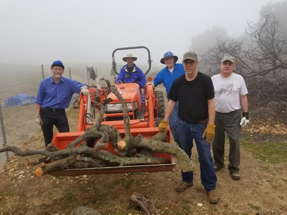 THE LOG TRANSPORT and storage team. (Left to right) Eric Turk, Sam Ervin, James Whedon, Bing Heckman and Jim Whitson. Not shown is Kyle Morrision who is at the storage area waiting to unload and stack this last bucket of logs. (Photo: Margaret Magnus, March 10, 2018)