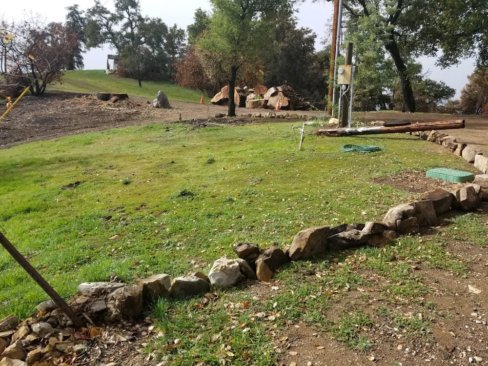 """THE ROCKS outlining the driveway and providing a protective barrier for the plumbing junction box. The removal of the old, rotten utility pole in the background is on a future """"to do"""" list. (Photo: Margaret Magnus, March 11, 2018)"""