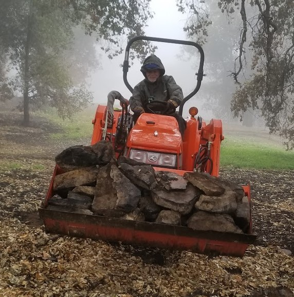 JAMES WHEDON taking a turn at the tractor to haul rocks that been hidden under the brush before the Thomas Fire. These rocks were used to create a more decorative barrier and outline the driveway. (Photo: Margaret Magnus, March 10, 2018)