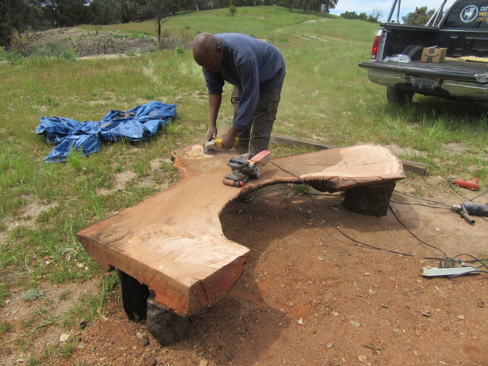 HAROLD GREENE finishing the top of the benches by sanding down the rough edges. (Photo: Sam Ervin, April 21, 2018)
