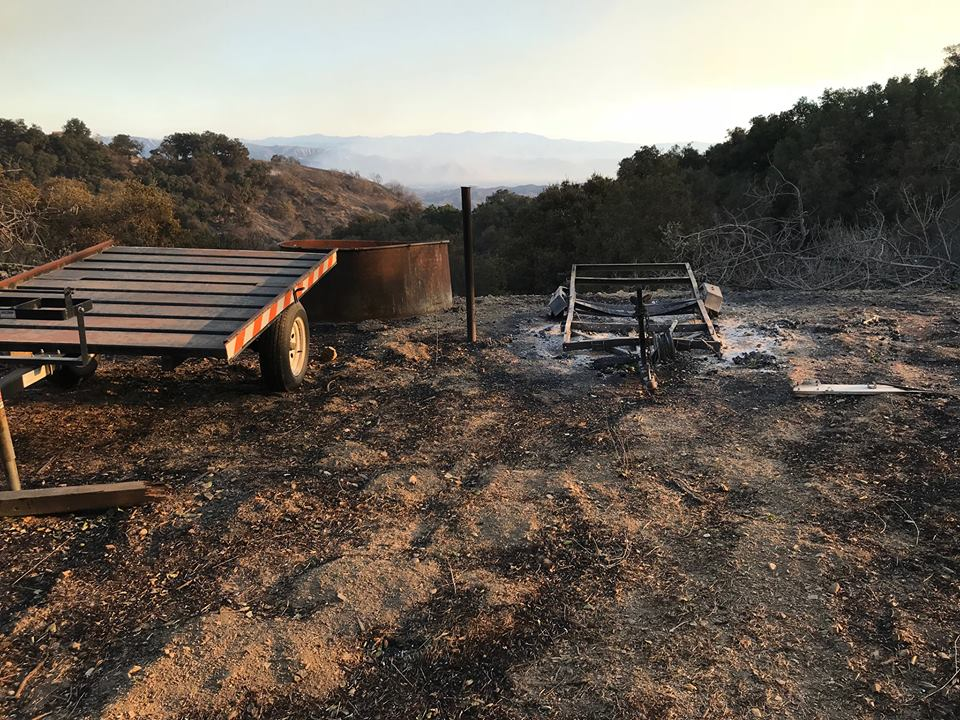 TWO TRAILERS - One survived the fire (left), and other did not (right). The burned wooden trailer belonged to Meher Mount. The metal trailer was purchased from Buzz Glasky and used extensively during wood harvesting and fire recovery. (Photo: Buzz Glaksy, December 2017)