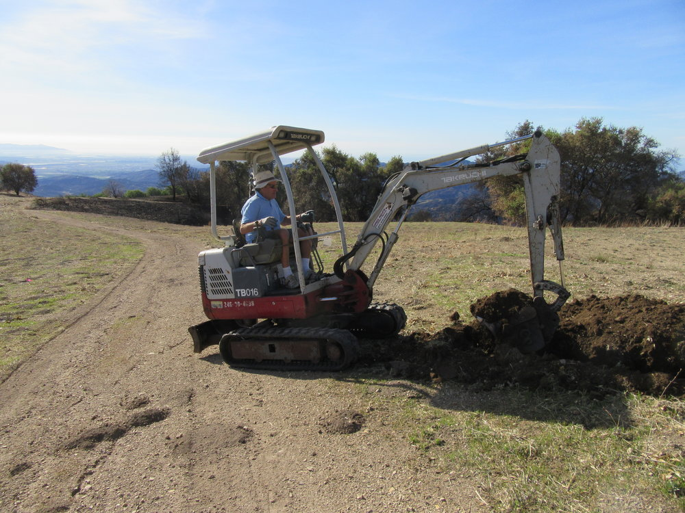 VOLUNTEER JIM AUSTER, a former board member, uses a trench digger at Meher Mount to create a 600-foot trench from the pool/reservoir to Baba's Tree to set up a watering system. (Photo: Sam Ervin, January 18, 2018)