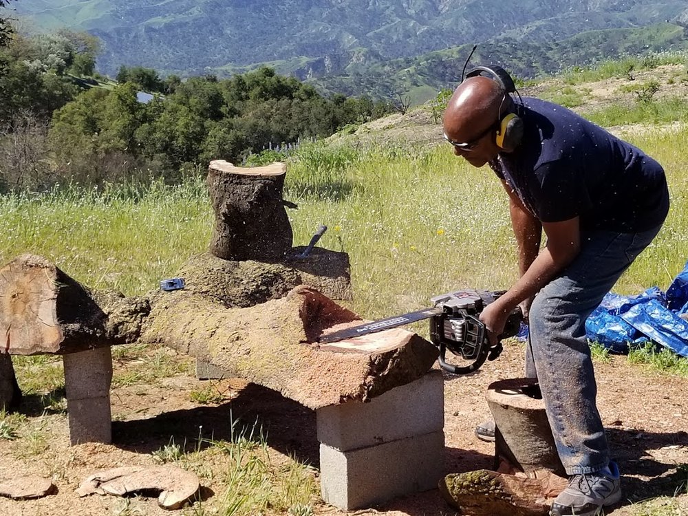 ARTISAN HAROLD GREENE cutting a space for the legs for the bench made from fallen wood of Baba's Tree at Meher Mount. (Photo: Margaret Magnus, April 20, 2018)