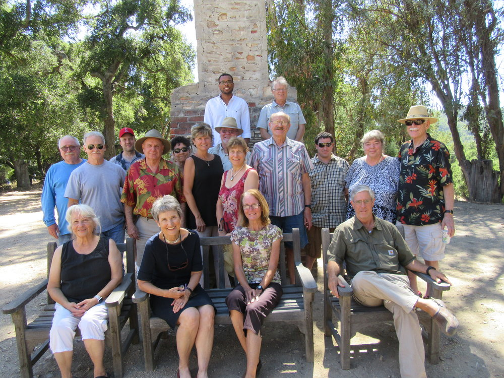 COMMUNITY MEETING 2017 to update Meher Mount's Master Plan. The group is in front of Baba's Fireplace before the Eucalyptus trees to the right burned in the December 2017 Thomas Fire and were later removed. (Top row, left to right) Ron Holsey, Robert Turnage; (Middle row, left to right): Buzz Glasky, Steve Bostwick, Brent Carter, Jim Whitson, Marta Flores, Nancy Pinckert, Byron Pinckert, Donnalyn Karpeles, Elliott Karpeles, Eric Van Buskirk, Ursula Reinhart, Richard Mannis; (Front row) Ginger Glasky, Margaret Magnus, Patti Jones, Bing Heckman. Not pictured is Sam Ervin who is taking the photo, July 22, 2017.