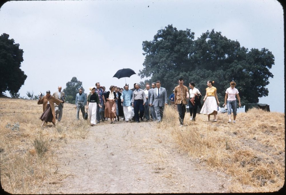AVATAR MEHER BABA (center, blue coat) walking with His followers at Meher Mount on August 2, 1956. Baba's Path and is kept mowed so that visitors can walk in His footsteps. (Photo: Darwin Shaw, (c) Meher Nazar Publications)
