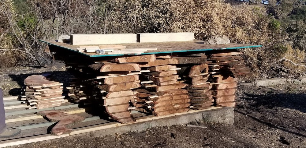 STACKED WOOD milled from the fallen limbs and branches of Baba's Tree. All the wood is being stored for future use while it cures. (Photo: Margaret Magnus, February 6, 2018)