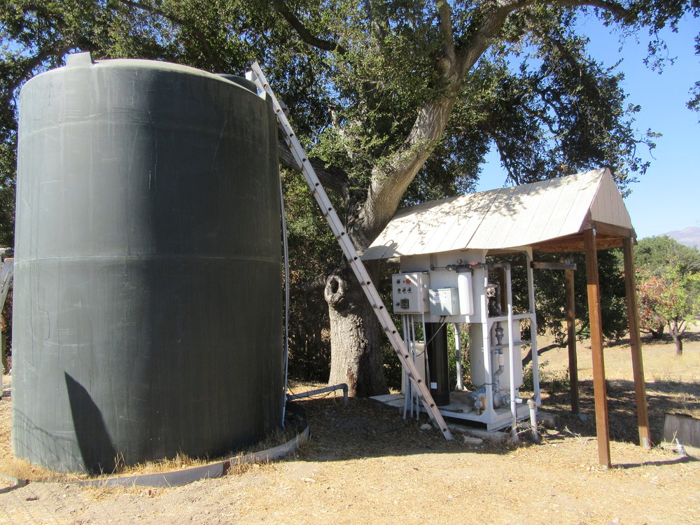 "ONE OF TWO WATER TANKS next to the upgraded water treatment system for Meher Mount's well water. This large tank holds potable water, while a smaller ""ag tank"" holds untreated water for watering plants at the Visitor Center and Baba's Tree. (Photo: Margaret Magnus, September 2018)"
