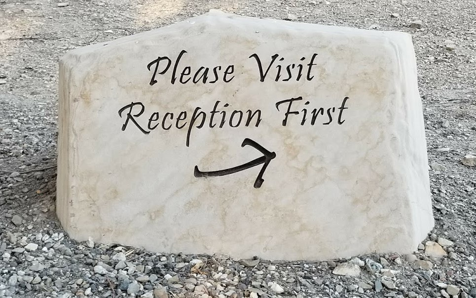 """ONE OF THE STONE SIGNS guiding visitors to check in at the reception area in the Visitor Center at Meher Mount. (See related story,  """"Stone Signs & Markers Are Installed."""" ) (Photo: Margaret Magnus, 2016)"""