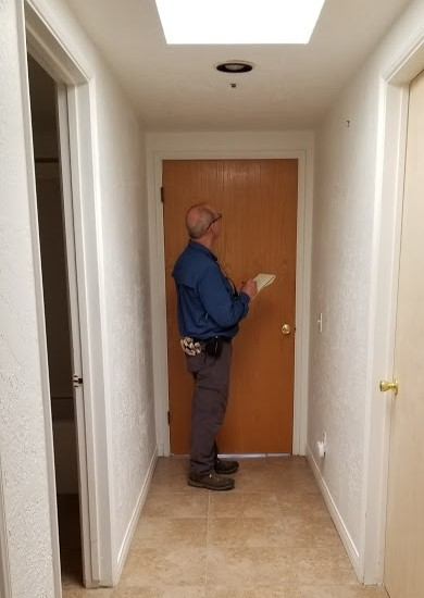SAM ERVIN writing specifications for the new closet built in this space after the door is closed off on both sides. (Photo: Margaret Magnus, June 21, 2018)