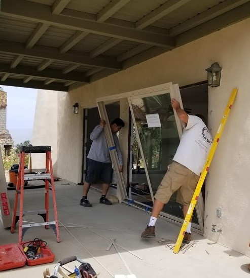 INSTALLATION OF A NEW SLIDING GLASS DOOR to the kitchen in the Caretaker Quarters at Meher Mount. The installers are from West Coast Sash & Door Inc. in Ventura, CA. (Photo: Sam Ervin, July 9, 2018)