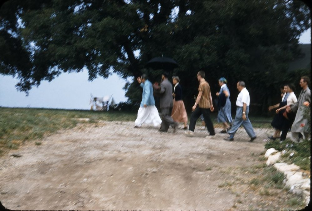 AVATAR MEHER BABA (blue coat) in 1956 at the start of the flagstone pathway leading to the guesthouse at Meher Mount. Over the years this walkway became covered with dirt and growth. There is an archaeological dig to uncover and preserve this touchstone of His 1956 visit. Eruch Jessawala, a close disciple, is carrying the umbrella. Meher Mount co-founder and lifetime caretaker Agnes Baron is close behind as is Tex Hightower, a professional dancer. (Photo: Darwin Shaw, 1956 (c)Meher Nazar Publications)