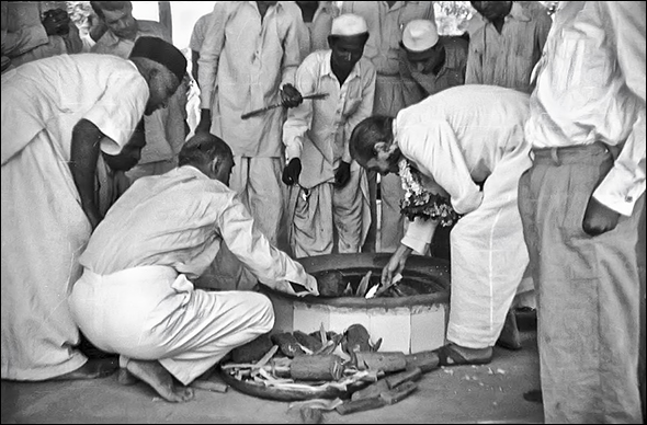 AVATAR MEHER BABA lights the  dhuni  in Meherabad, India, home of His Tomb Shrine in the 1950s. (Photo: MN Publications)