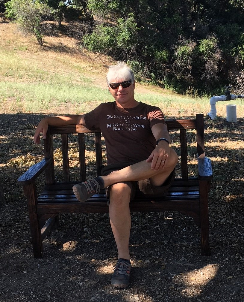 ERIC CARLSON relaxing for a moment after he and Ellen Kwiatkowski have refurbished and stained all the wood benches and chairs at Meher Mount. (Photo: Ellen Kwiatkowski, July 2019)