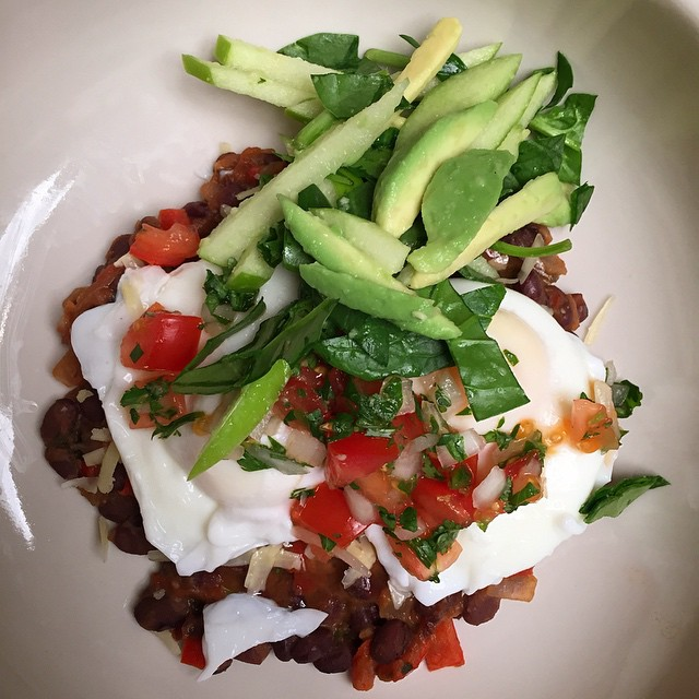 Poached eggs over spiced black beans, with pico de gallo and an avocado apple spinach salad.