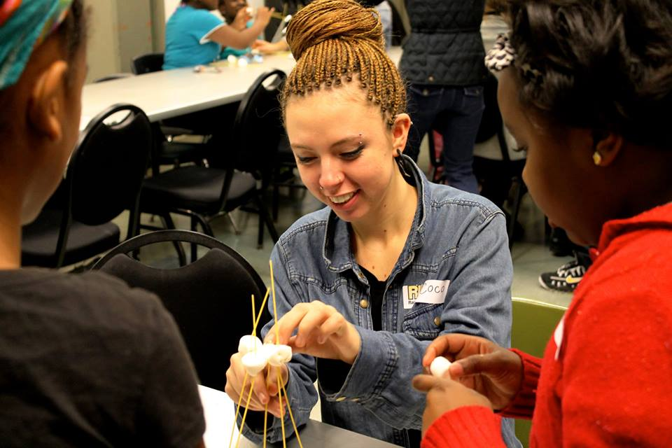 Corine Rosenberg working with kids at Raquet Up Detroit building the tallest marshmallow tower!