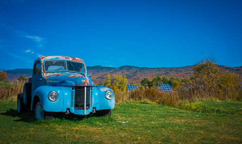 A truck surrounded by solar panels in the fields at the Cider Mill