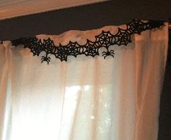 felt spider garland hung from a curtain rod