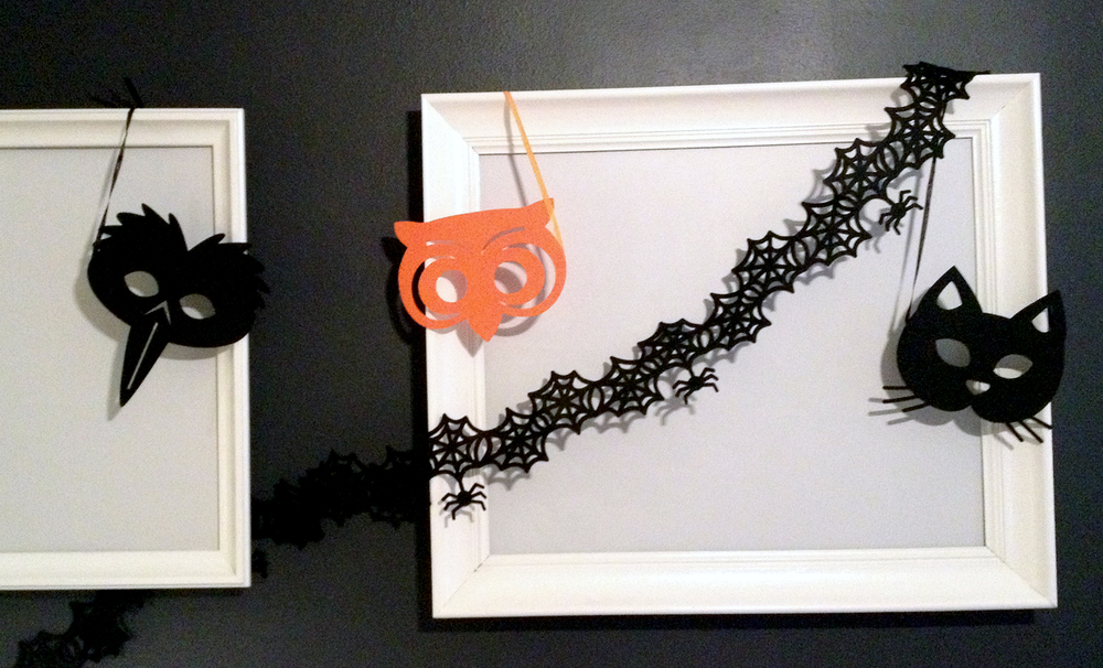 masks and garlands strung from picture frame corners
