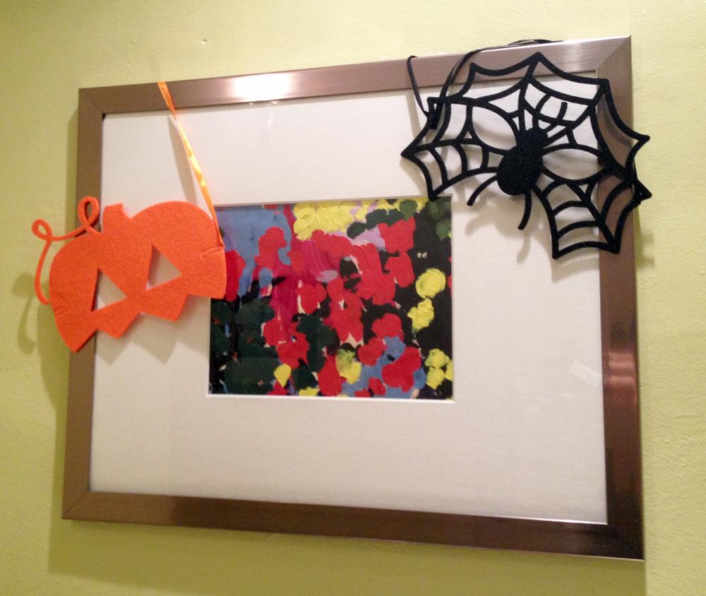 felt masks hang over picture frame corners