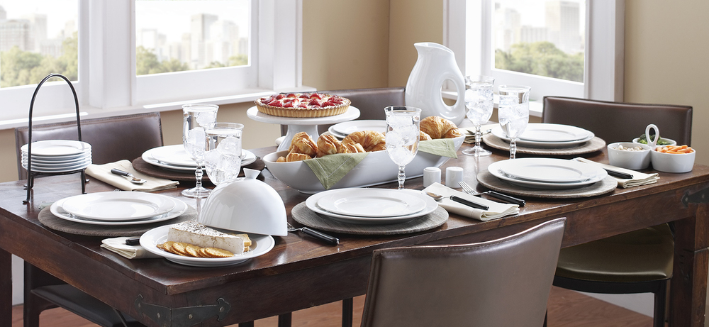 an elegant mix: understated table set with crisp whiteware and natural hyacinth chargers