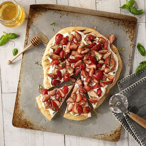 Pizza and strawberries, count me in! This dessert is perfect for a summer cookout with grilled pizza crust, cream cheese spread, and fresh strawberries tossed with honey and basil. YUM!   Photography and recipe found at:  readyseteat