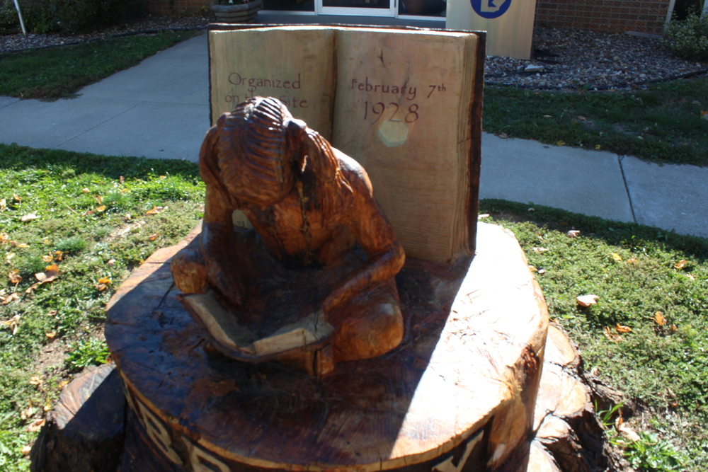 The statue carved out of an old tree in front of the Montrose library