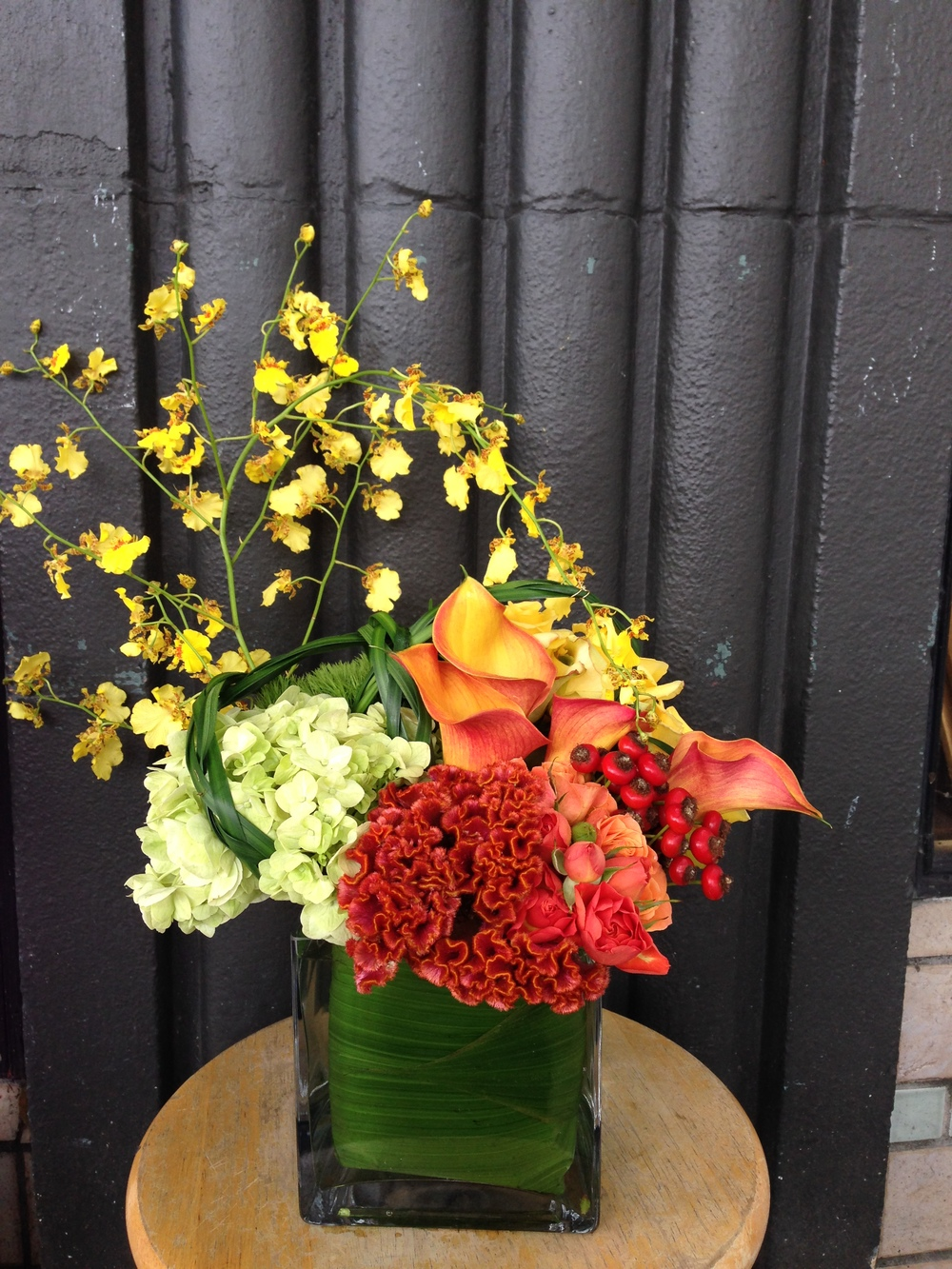 Brilliant rooster comb, calla lilies and 'dancing lady' orchids come together for a robust fall palette