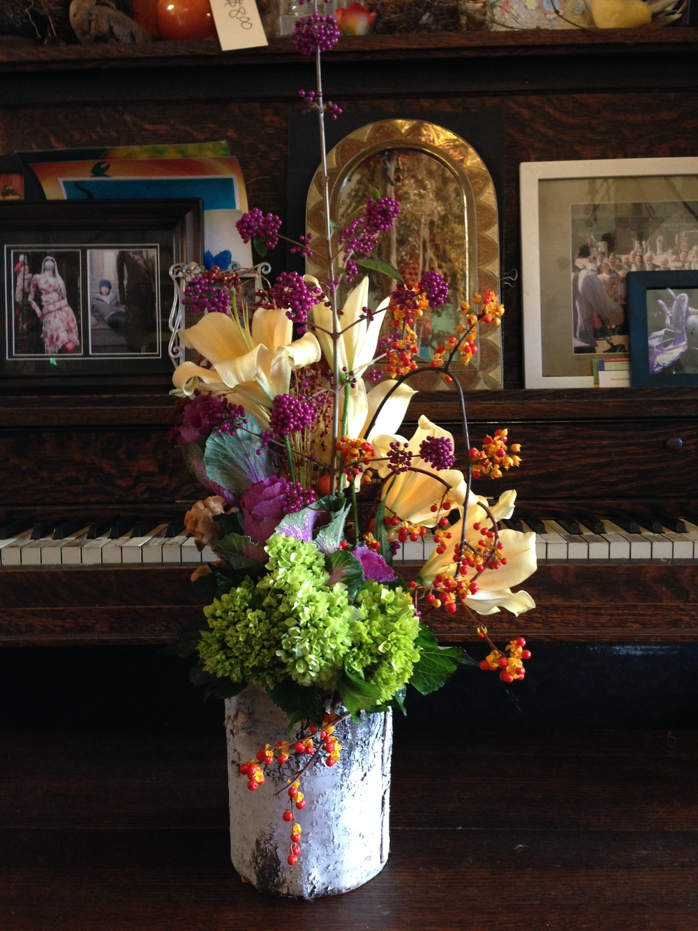 Birch bark-covered vase gives this arrangement a natural, woodsy appeal.