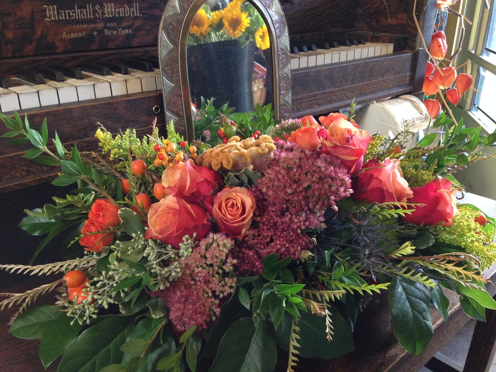 'Cherry brandy' roses, grevillea, and sedum are lush and abundant in this woodsy arrangement