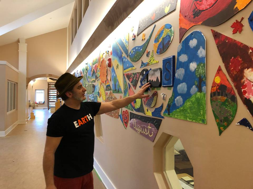 Anthony Zito looks over the art project he helped the children of Hollis Montessori School to create.