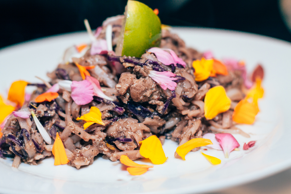 Entrée: Jerk marinated chicken cutlet on rice noodles, whole eggs, hoisin-jerk sauce, shredded purple cabbage, bean sprouts, & eatable flowers. Photos courtesy of:  Nathalia Allen –  AMillionMinds.ca  ( @amillionminds )