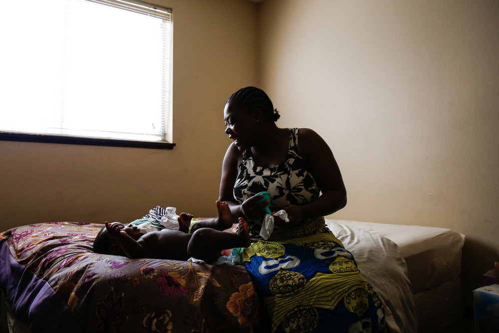"Bebe changes Prayer in the bedroom of their apartment that they share with another single Congolese woman. Since moving to the U.S., Bebe has either been pregnant or a new mother. She's expressed a strong desire to work, but is being held back by her normal motherhood hesitancies. ""I like to spend time with Prayer,"" she shares.  ""But I need to work soon. I cannot just sit here."""