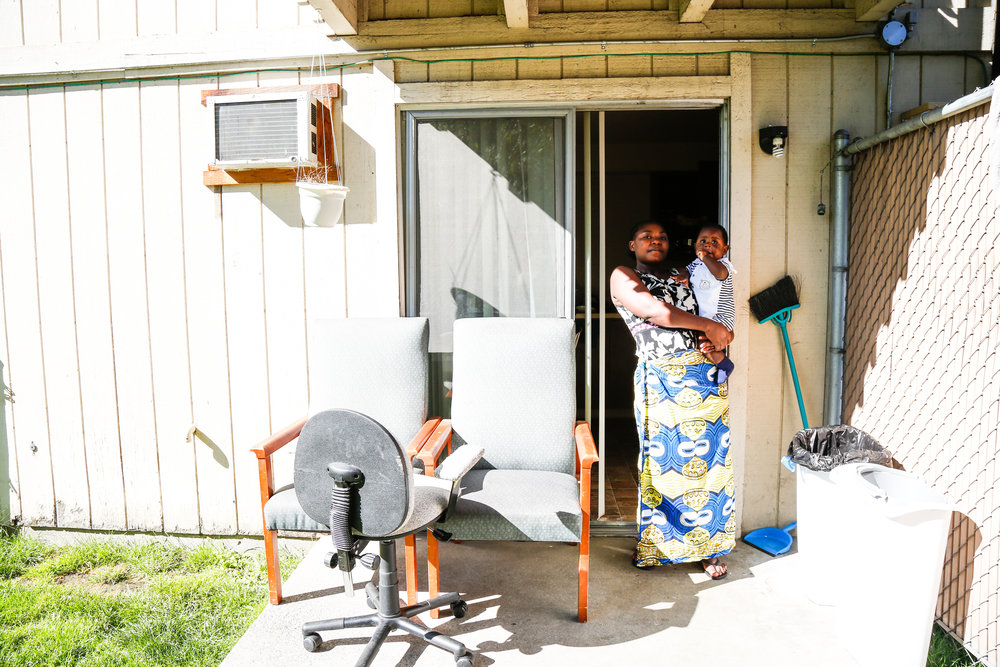 "Bebe and Prayer pose on their apartment's back porch. When asked what advice she would offer to other single refugee mothers, Bebe responds: ""They need to be humble. And love everybody."" She then adds, ""They should follow the laws. If you follow the laws in America, you will be okay."""