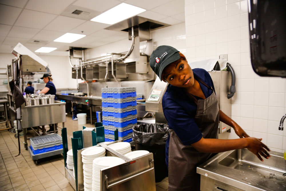 "Judith washes her hands before beginning her shift as a dishwasher. ""Everyone knows I work hard,"" Judith says. ""The smells here make me sick, but what can I do – I must work for my family."""