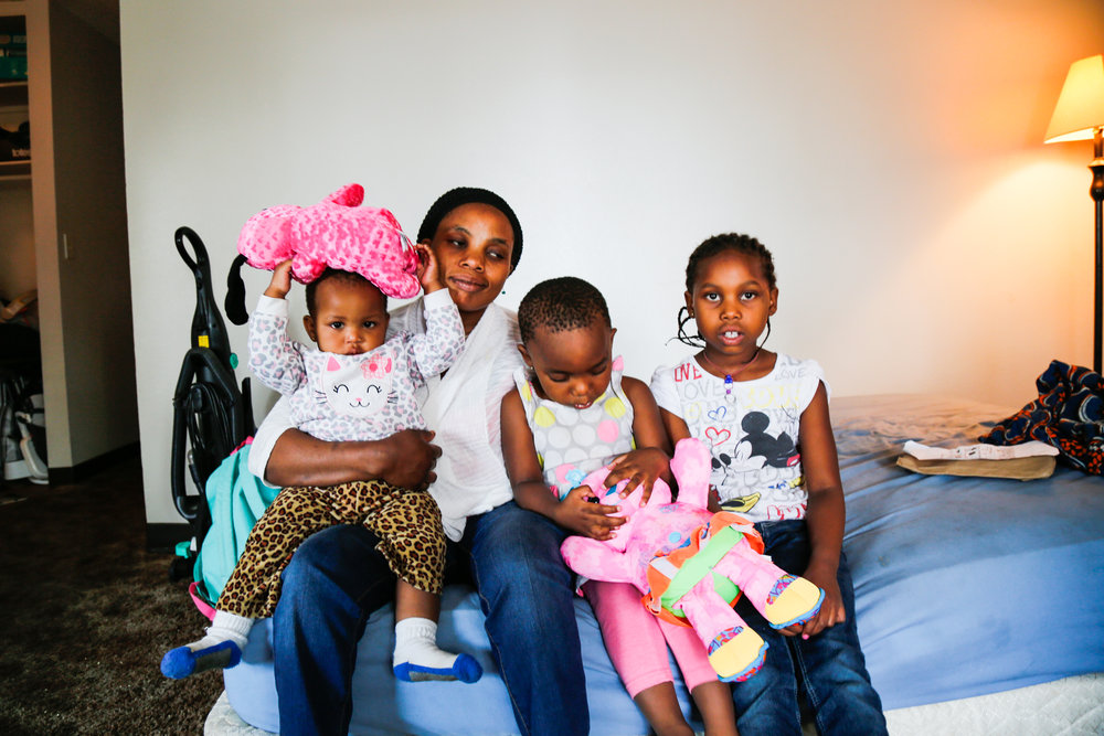 Juju poses on a mattress in her apartment livingroom with her three daughters – Grace, Phoebe and Janet. Every day she busses between work, childcare, elementary school, and her apartment. Because she lives alone, building a new community has proven to be quite challenging.