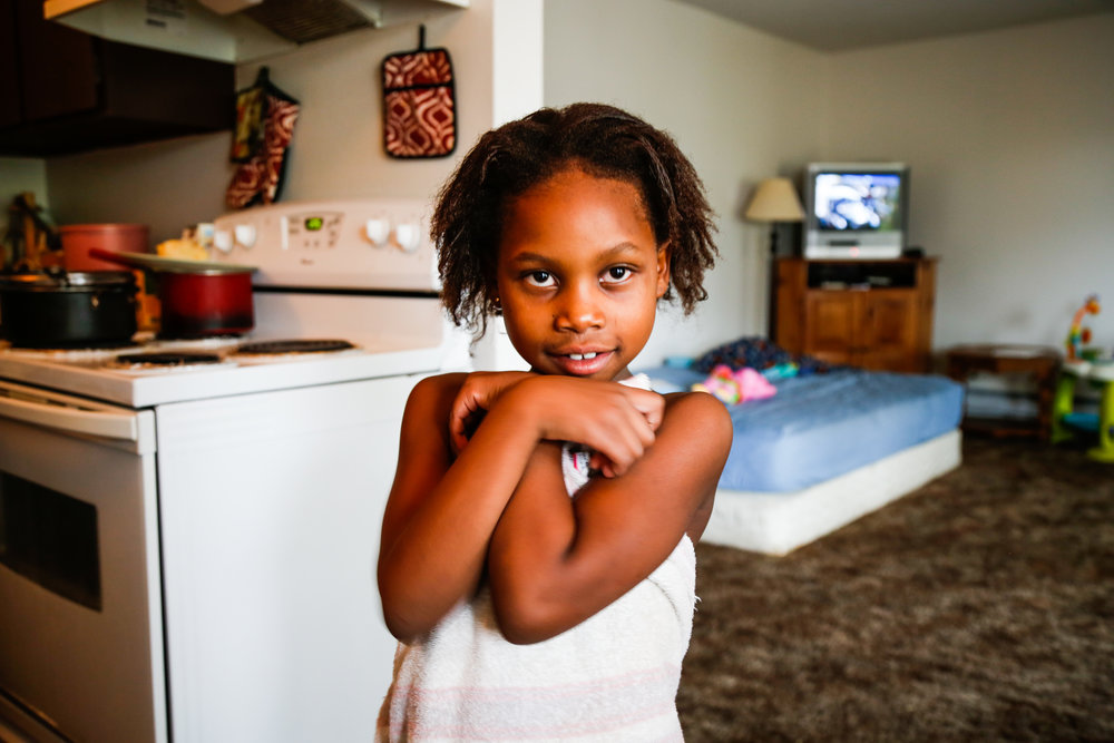 Janet, Juju's eldest, poses post-shower while waiting for her mother to braid her hair. Despite her shy appearance, Janet is a ball of confidence and spunk. At the age of six, she frequently serves as her mother's interpreter.