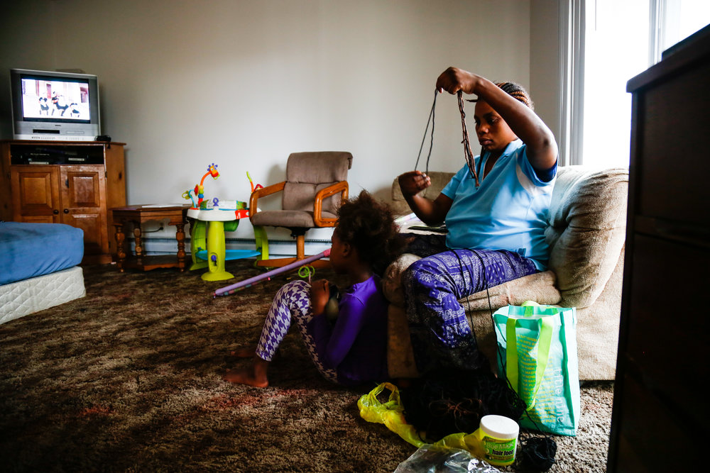 It's a rainy Saturday afternoon and Juju has just finished cleaning her apartment. She now prepares to braid Janet's hair, a process that can take up to three hours. As a single mother of three girls, braiding hair can feel like a daunting chore, but it's one that makes her girls feel loved.