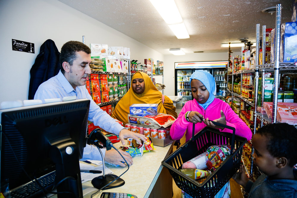 "Sudi, Asha, and Yakub shop at the local Arabic market. Owned and operated by a Syrian family, the market offers items such as Halal meat and pre-made samosas. ""It is not cheap, but it's our food,"" shares Sudi."