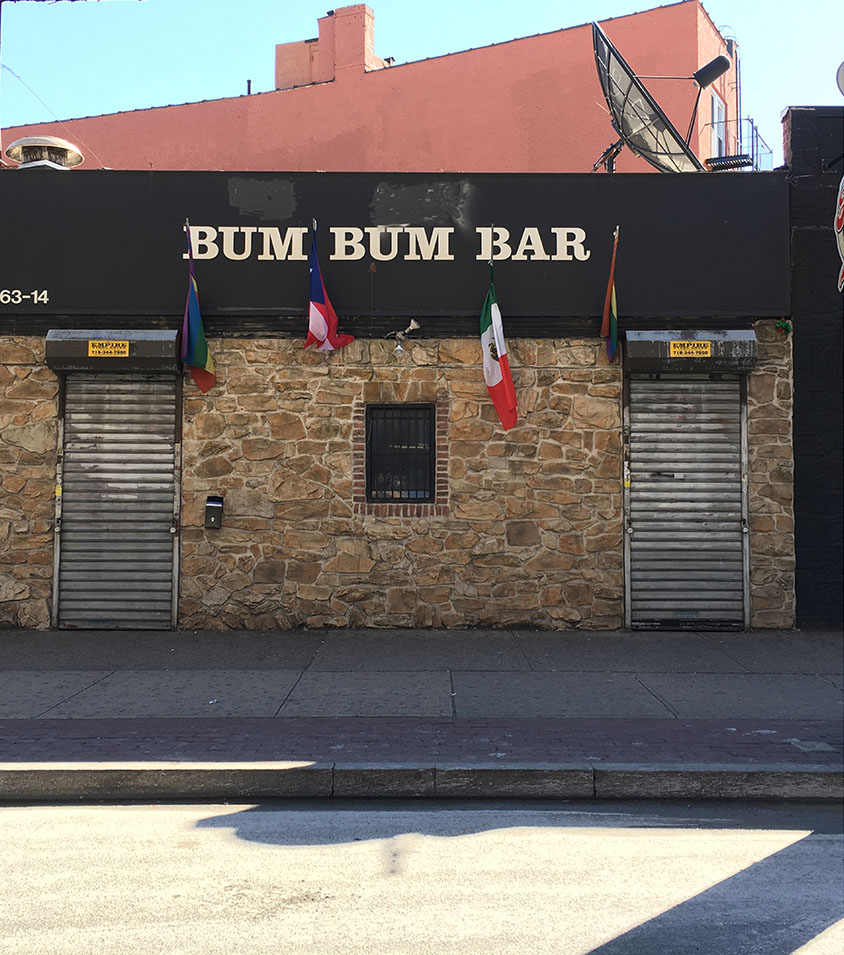 "BUM BUM BAR 63-14 ROOSEVELT AVENUE, QUEENS, NY OPEN EARLY 1990S-PRESENT (BUM BUM BAR, PICTURED) ""Queens hotspot Bum Bum Bar is now third-generation gay-owned: New owner Danny Hart has taken the torch passed to her from the bar's previous leading lady, Connie Idavoy. On Saturday, March 12, Hart threw a huge party to honor her predecessor, Idavoy — and usher in a new era for Bum Bum Bar. At Hart's hotly anticipated party, dancers/shot girls Jasmine and Stephanie served free Jell-O shots topped with whipped cream, and of course, danced for the crowd. Two bucks got guests a Fireball shot to spice up their night. In an exclusive interview with GO prior to the party, Hart revealed that the event doubled as a birthday bash, complete with cake and a 'happy birthday' serenade courtesy of Bum Bum bar. DJ Doli, a 22-year Bum Bum vet, spun sexy Latina grooves well into the wee hours. Hart explained in her convo with GO the origin of the now-legendary Bum Bum Bar's name. 'The word 'Bum Bum' is actually Brazilian. It means 'the booty of the women,' said Hart. 'In Brazil they have a contest called the Bum Bum Contest, and it takes into account the whole physique of the woman, including the butt and waistline.' The two gay men that opened Bum Bum Bar named it after the contest in homage to their beautiful women customers. The venue has since become a Queens community fave and continues to crank out countless events and bar specials that draw party-goers from all five boroughs. Popular nights include 'Wacky Wednesdays' and 'Throw Back Thursdays ,'  both offering a 5-8pm happy hour and no cover charge. Saturdays at Bum Bum are now 'Sabado de Rumba Total,' and 'Bingo Fun Sundays' come complete with karaoke, a 5-8pm happy hour and no cover charge. Bum Bum's doors open at 5pm and don't shut 'til 4am. The new Bum Bum Bar boasts some svelte new décor and features a back patio that allows for cookouts on warm summer nights and serves as a space for smokers in colder months. If you want to celebrate your birthday at Bum Bum, they offer a special package that includes cake (with sparklers on top!) and singing. They also handle all the decorations and add sparklers to said cake for extra flair. Bum Bum's maximum capacity is 175 people, so you can easily invite your entire crew out to celebrate. Prior to taking the reins at Bum Bum Bar, Danny Hart served our country and city in the Army and as an NYPD officer, respectively. Hart has always demonstrated a strong commitment to giving back, and her goal of ensuring that Bum Bum Bar proudly caters to the lesbian community she deeply cares for should prove no different. While putting her own spin on things at Bum Bum, Hart says she plans to continue some of Idavov's traditions, such as a huge Pride party and a giant New Year's soiree with complementary bottles of champagne. Saturday's party was only the beginning of what's sure to prove an amazing era at Bum Bum bar, reborn with Danny Hart at the helm. Drop in Bum Bum soon, shake Hart's hand, and let her welcome you into the Bum Bum Bar family."" (Shea Carmen Swan, Go Magazine, 2016)"