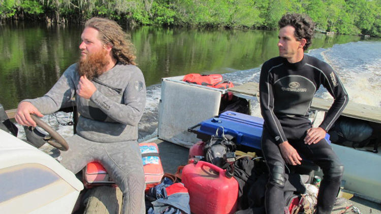 "Hewitt Emerson, left, and Justin Herrington look for ""sinker wood"" aboard a barge on the Edisto River in South Carolina. (David Zucchino / Los Angeles Times)"