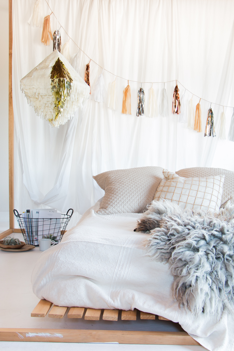 A day bed made extra dreamy with a  Neutral Tassel Garland  and  Ivory and Gold Shag Piñata . Both by  Prospect Goods .