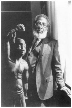 Lolis Elie, standing next to a statue of a Maroon, a slave who  refused to be enslaved by the French in the Caribbean, 1984. Courtesy New Or_4.jpg