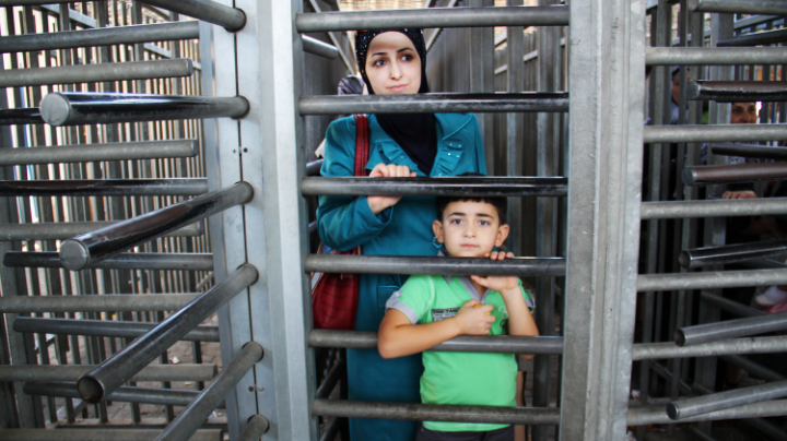 "Mother and son, at the  Qalandia checkpoint , the main crossing between Palestinian villages in the northern West Bank and Jerusalem.    Photo: NPR.        Normal   0           false   false   false     EN-US   X-NONE   X-NONE                                                                                                                                                                                                                                                                                                                                                                           /* Style Definitions */  table.MsoNormalTable 	{mso-style-name:""Table Normal""; 	mso-tstyle-rowband-size:0; 	mso-tstyle-colband-size:0; 	mso-style-noshow:yes; 	mso-style-priority:99; 	mso-style-parent:""""; 	mso-padding-alt:0in 5.4pt 0in 5.4pt; 	mso-para-margin-top:0in; 	mso-para-margin-right:0in; 	mso-para-margin-bottom:10.0pt; 	mso-para-margin-left:0in; 	line-height:115%; 	mso-pagination:widow-orphan; 	font-size:11.0pt; 	font-family:""Calibri"",""sans-serif""; 	mso-ascii-font-family:Calibri; 	mso-ascii-theme-font:minor-latin; 	mso-hansi-font-family:Calibri; 	mso-hansi-theme-font:minor-latin;}"