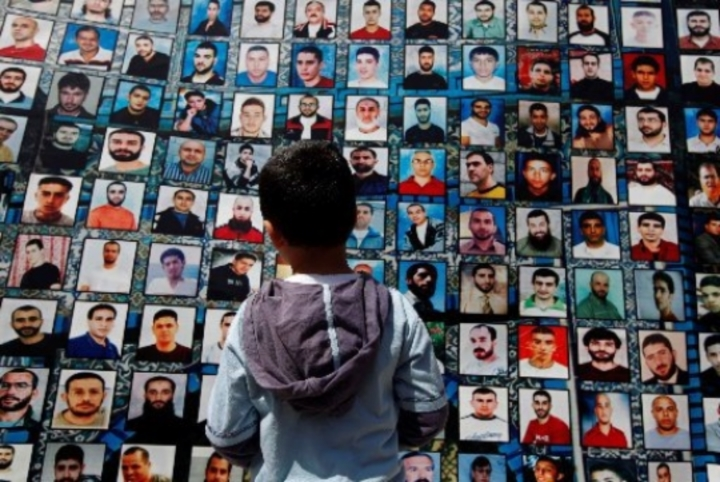 A Palestinian boy looks over a wall full of men.