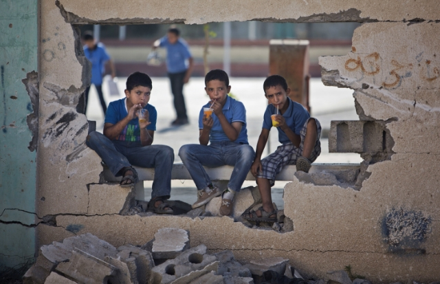 Palestinian boys, looking through a damaged school wall in Gaza City. Photo: Khalil Hamra/AP.