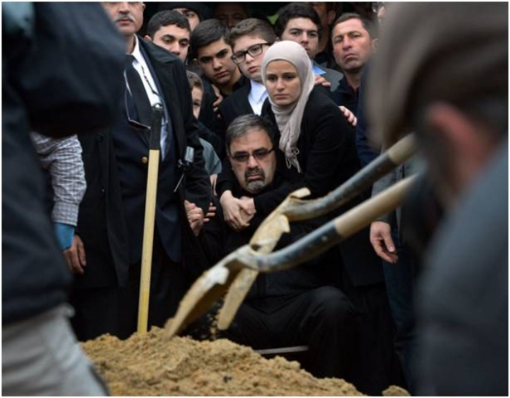 Namee Barakat (center), the father of Deah Shaddy Barakat, puts his son into the ground.